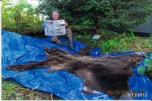 Bob Bergmeyer, of Canton, Ohio, takes a break to read Farm and Dairy while bear hunting in Cordova, Alaska. Bergmeyer spent his birthday in Alaska, hunting brown bear and moose. He got a bear his second day out, but while he was out hunting moose later, the bears ransacked his campsite. He still had a good time visiting with friends -- and he came home with a bear and about 50 pounds of halibut!